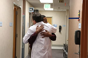 Kemal Hebano hugs Cyril Mauffrey Denver Health