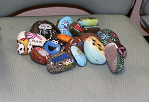 Margie Garcia paints rocks and leaves them at Denver Health